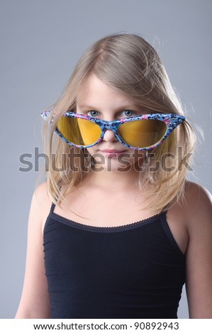 Little girl in funny big glasses in studio. - stock photo