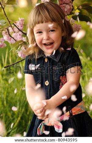 Little girl in garden, under the sakura tree. Spring petal's rain. - stock photo