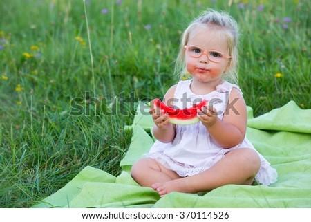 Little girl in glasses eating water-melon  - stock photo