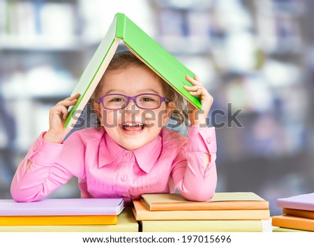 Little girl in glasses under roof made from book. - stock photo
