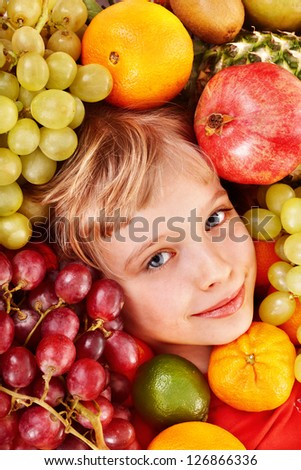 Little girl in group of fruit. Healthcare.