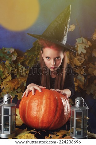 Little girl in halloween costume of the witch with the pumpkin and lantern make spell conjure