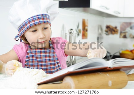 Little girl in hat and apron preparing cookies with cookbook - stock photo