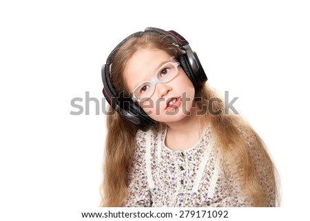 little girl in headphones listens to music - stock photo