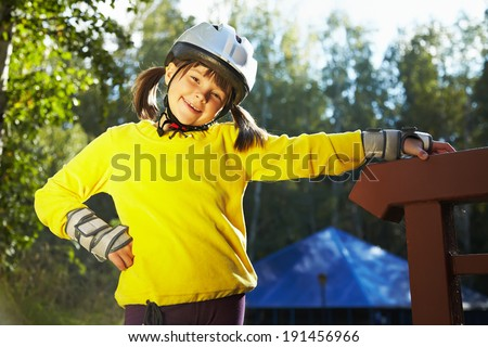 Little girl in helmet and roller skates at a park. child outdoors - stock photo