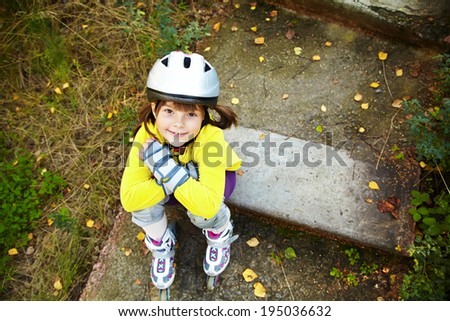 Little girl in helmet and roller skates at a park. children outdoors - stock photo