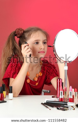 little girl in her mother's dress, is trying painting her eyelashes