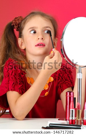 little girl in her mother's dress, is trying painting her eyelashes - stock photo