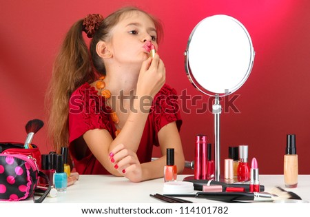 little girl in her mother's dress, is trying painting her lips