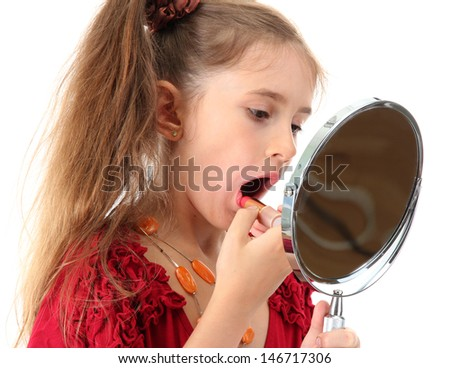 little girl in her mother's dress, is trying painting her lips, isolated on white - stock photo