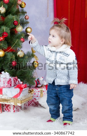 Little girl in jeans and a sweater standing beside a Christmas tree and points a finger at her - stock photo
