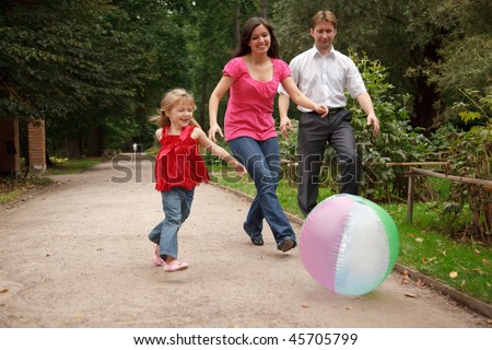 Little girl in jeans and red dress plays with big inflatable ball in park together with parents. - stock photo