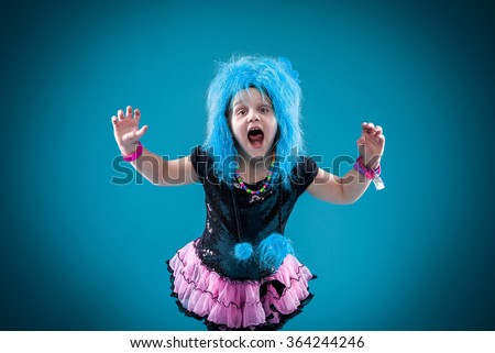 Little girl in monster hat roaring at the camera. Pink tutu with black top. Blue hat - stock photo
