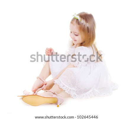 Little girl in mother's shoes on white background - stock photo