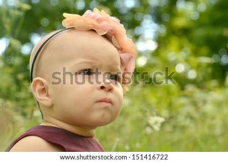Little girl in park with flower on her head
