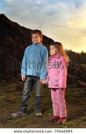 Little girl in pink clothes and boy in blue jacket standing near hill at evening