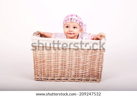 little girl in pink cute hat sitting at the basket
