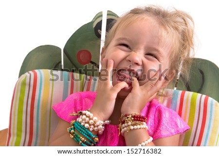 Little girl in pink dress with excessive jewelry sitting and laughing isolated on white