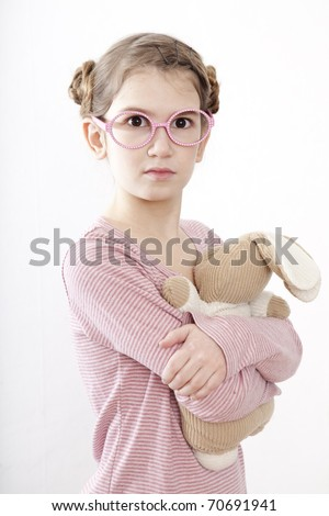 Little girl in pink glasses nine years old  hugging her loved toy - stock photo