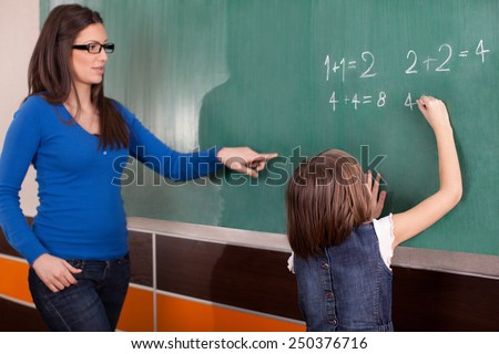 Little girl in primary school writing mathematics task on chalkboard while teacher looking at her - stock photo