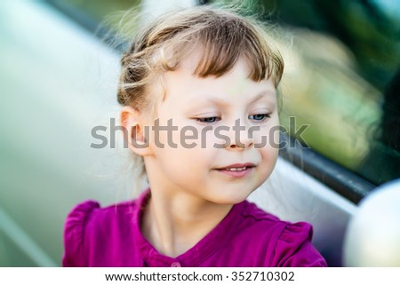 little girl in purple dress admires itself in the mirror of the car