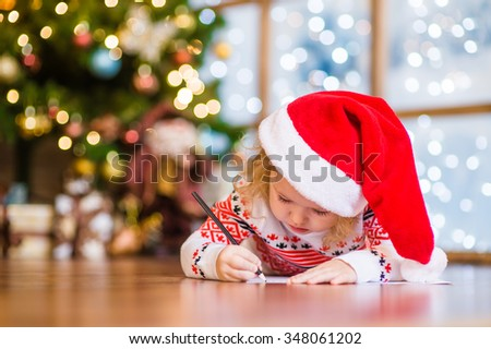 Little girl in red christmas hat writes letter to Santa Claus - stock photo