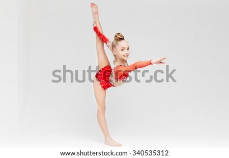 Little girl in red dress doing standing split over white background. - stock photo