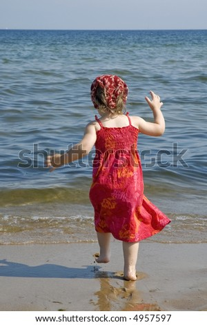 little girl in red dress on the beach - stock photo