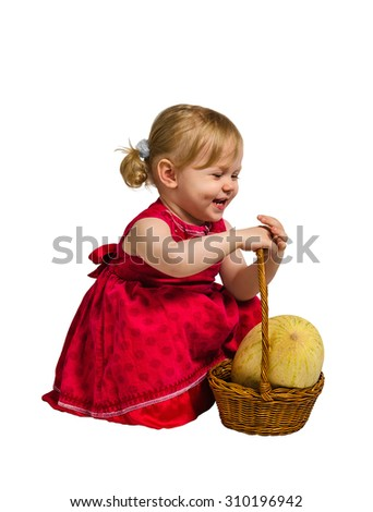 Little girl in red dress sitting on his haunches next to the basket, which is a large yellow melon