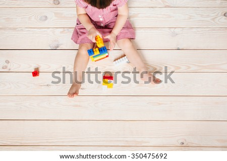 little girl in red dress sitting on the wooden floor and playing Lego. Top view - stock photo