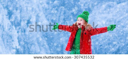 Little girl in red jacket and green knitted hat catching snowflakes in winter park on Christmas eve. Kids play outdoor in winter forest. Children catch snow flakes on Xmas. Large size panorama banner - stock photo