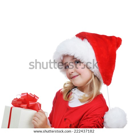 little girl in red santa cap  holding christmas present  - stock photo