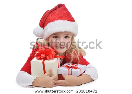 little girl in red santa cap with christmas presents