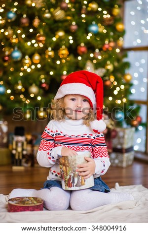 Little girl  in red santa hat holding christmas gift box