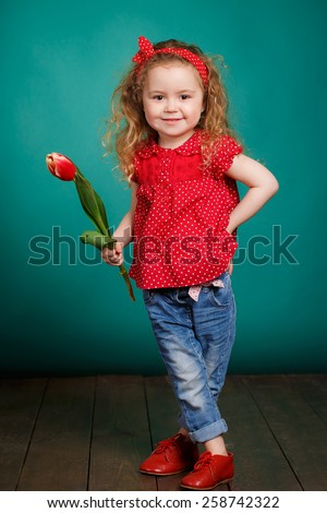 little girl in red shirt with red tulip. Happy child. Studio portrait. Congratulations consept.   - stock photo