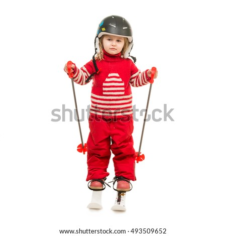 little girl in red ski suit standing on skis with ski poles and in helmet isolated on white background