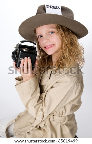 Little girl in reporter costume holding antique camera - stock photo
