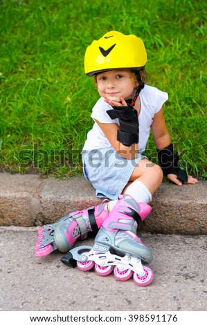 Little girl in roller skates in park at summer. Pretty child, kid riding a roller. Portrait of cheerful preschool girl wearing roller skates and protective equipment. - stock photo