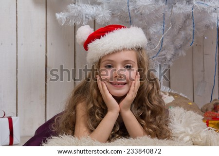 Little girl in Santa Claus hat dreaming over christmas fir tree - stock photo