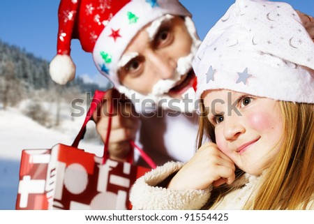 Little girl in santa hat and santa claus in background - stock photo