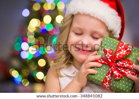 little girl in Santa hat holding a present under the Christmas tree - stock photo