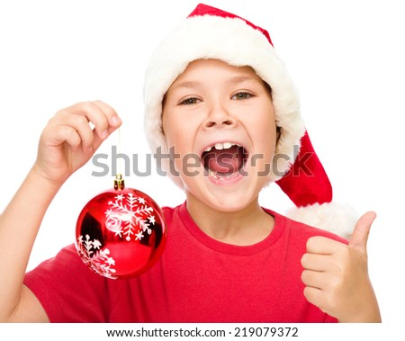 Little girl in santa hat is holding a christmas decoration and showing thumb up sign, isolated over white - stock photo