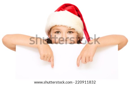 Little girl in santa hat is holding blank board and pointing to it using index finger, isolated over white - stock photo