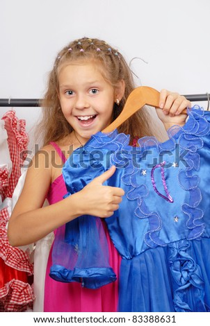 Little girl in shop of dresses and hand shows sign OK - stock photo