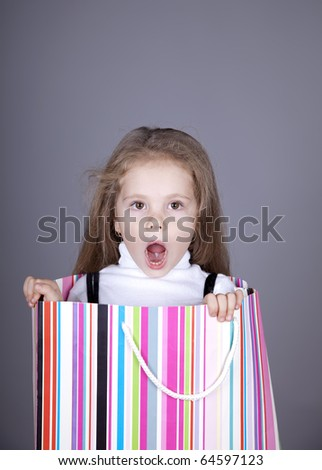 Little girl in shopping box. Studio shot. - stock photo