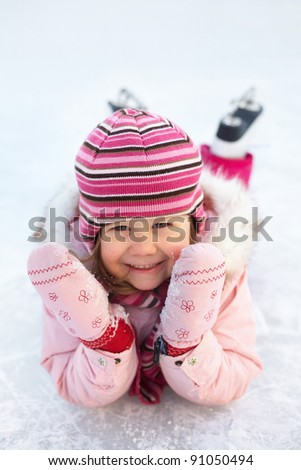 little girl in skates on the ice rink lies and laughs - stock photo