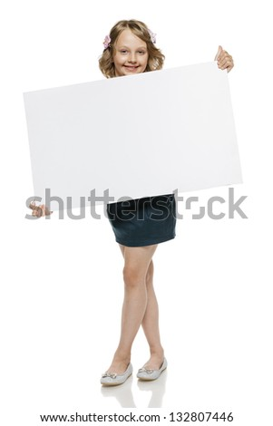 Little girl in summer clothing in full length holding blank whiteboard, isolated on white background - stock photo