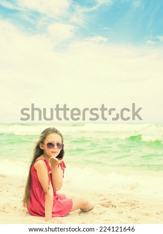 little girl in sunglasses sending a kiss while sitting at the seaside - stock photo