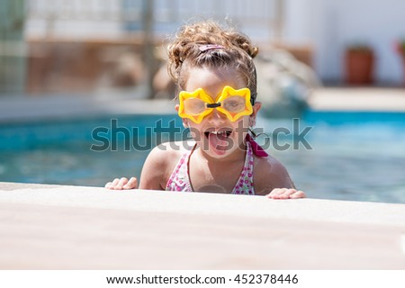 Little girl in swimming pool wearing goggles