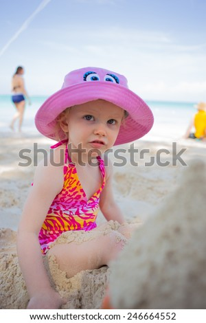 Little girl in swimsuit playing in the sand on a beach - stock photo